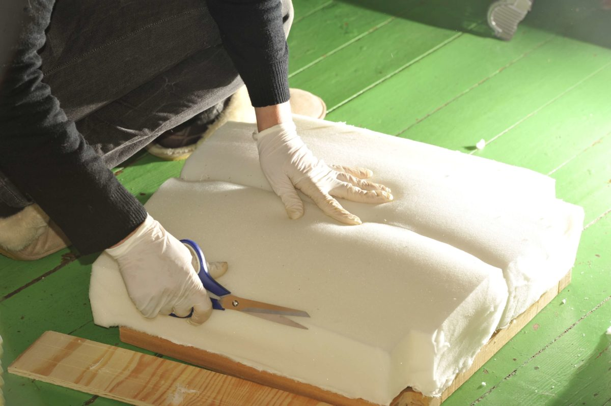 A woman reupholsters a kitchen stool using scissors to trim the foam